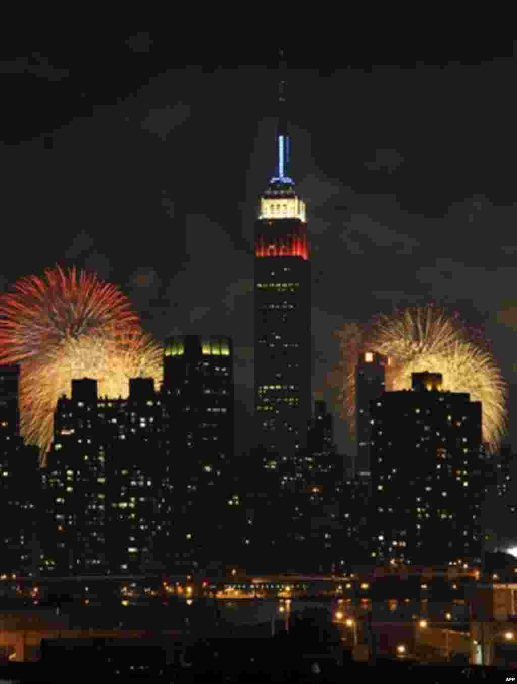 The Empire State Building, illuminated with red, white and blue lights, is seen from across the East River in the Queens borough of New York, as fireworks exploding over the Hudson River during the Macy's Fourth of July fireworks show on Monday, July 4, 2