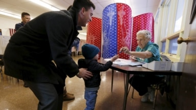 An election official (R) takes a voting token which shows that a voter has checked in and is eligible to vote from young Bryan Townsend (C) before handing his father a blank ballot to mark his vote in New Hampshire's presidential primary election, Feb. 9,