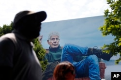 "People walk past a billboard for the CNN television show ""Parts Unknown"" with American celebrity chef Anthony Bourdain, Friday, June 8, 2018 in Atlanta, Georgia."