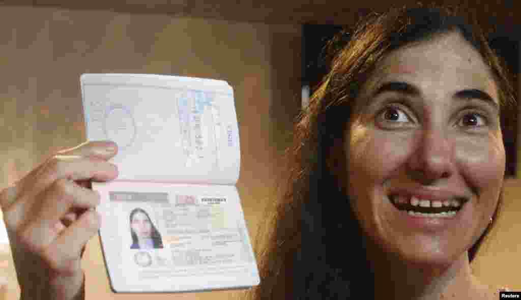 La bloguera cubana Yoani Sánchez posa junto a su pasaporte al llegar al aeropuerto internacional Guararapes en Recife, Brasil proveniente de La Habana, Cuba, el lunes 18 de febrero.