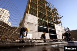 ARCHIVO-Obreros trabajan en un sitio de construcción en Teherán, Irán, el 20 de enero de 2016. El presidente iraní, Hassan Rouhani, dijo el 8 de mayo de 2018 que Estados Unidos no podría perjudicar a la economía iraní volviendo a imponer sanciones relacionadas con la energía nuclear.