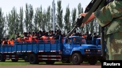 FILE - Criminals and suspects are transported to a stadium for a mass sentencing rally in Yili, Xinjiang Uighur Autonomous Region, May 27, 2014.