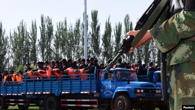 2014年5月27日,新疆伊犁武装警察正在把一批犯罪嫌疑人押送到群众大会上公审判决。