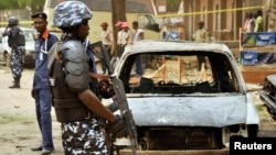A policeman stands near damaged vehicles after a suicide car bomber killed five people on a street of popular bars and restaurants in Sabon Gari, Kano, Nigeria, May 19, 2014.
