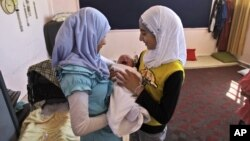 Syrian girls, who fled their home in Anadan with their family hold their relative Mohammed Mustafa who was born five days ago in a school in Kafar Hamra, Syria, August 22, 2012.