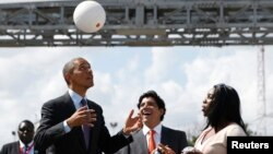 "FILE - U.S. President Barack Obama bounces a soccer ball with his head at Ubungo Power Plant in Dar es Salaam, July 2, 2013. The ball, called a ""soccket ball,"" has internal electronics that allow it to generate and store electricity that can power small devices."