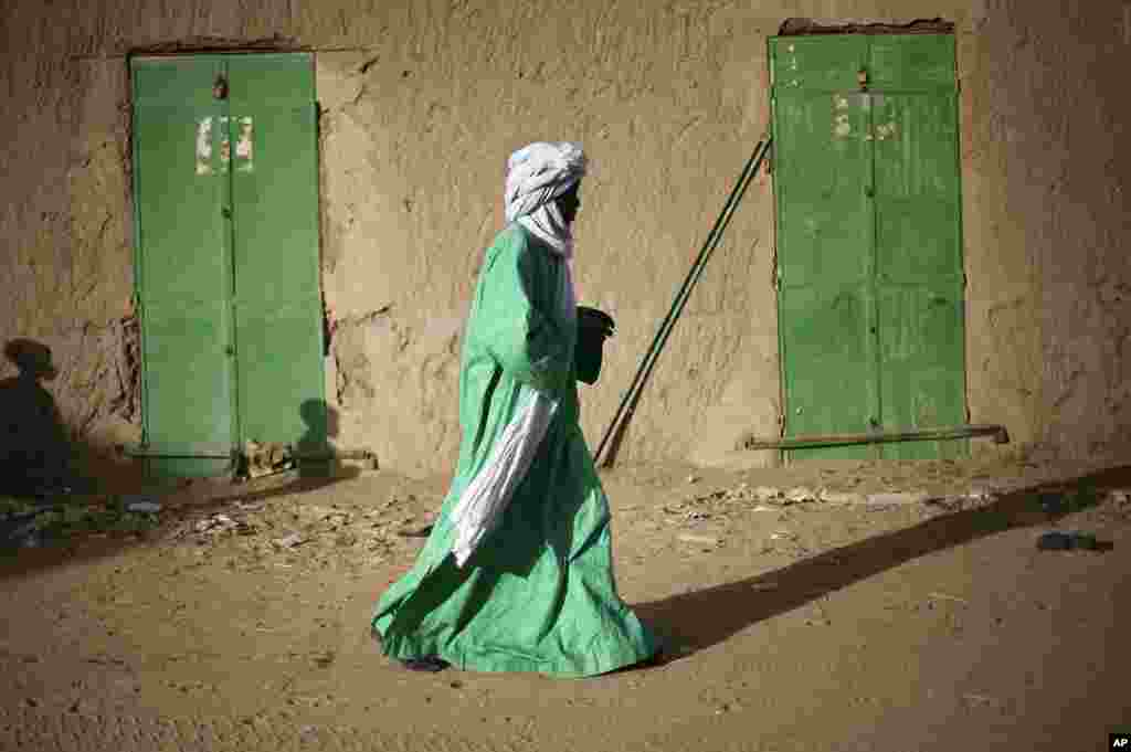 A Malian man walks between doors of closed shops in Gao, northern Mali, February 5, 2013.