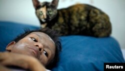 In this file photo, Samruei, a terminally ill Thai woman rests with her cat at a hospice for those dying of AIDS at a Buddhist temple Wat Prabat Nampu in Lop Buri.