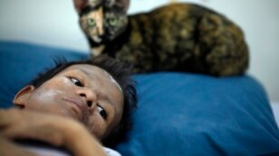 FILE - Samruei, a 35 year-old terminally ill Thai woman rests with her cat at a hospice for those dying of AIDS at a Buddhist temple Wat Prabat Nampu in Lop Buri.