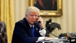 FILE - President Donald Trump speaks on the telephone in the Oval Office of the White House in Washington, Jan. 28, 2017. On Wednesday, Trump spoke with Saudi King Salman.