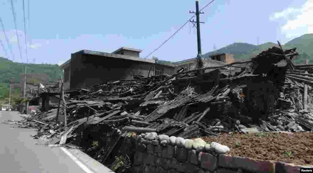 Collapsed houses are seen after an earthquake of 6.6 magnitude, on the side of a road leading from Ya'an city to Luzhou county, in Ya'an, Sichuan province, Apr. 20, 2013.