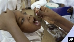 FILE - A health worker gives a child an oral polio vaccine in Kano, Nigeria.