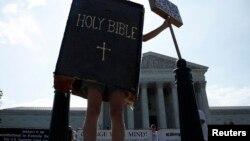 30일 미국 워싱턴 대법원 앞에서 한 운동가가 성경책 모양을 한 채 낙태 반대 시위를 하고 있다.