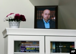 A portrait of Yalqun Rozi is seen atop a bookcase in his son and wife's apartment Thursday, April 18, 2019, in Philadelphia. (AP Photo/Jacqueline Larma)
