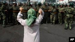 资料照:在西方记者访问乌鲁木齐一处地段之际,一名维吾尔妇女在中国武警面前要求释放被捕的维吾尔人。(2009年7月7日)