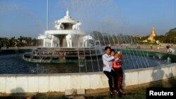 ຊາວມຽນມາສອງຄົນ ກຳລັງຖ່າຍຮູບເອົາຕົນເອງ ໃນວັນສຸດທີ່ຮັກ ໃກ້ໆກັບວັດ Shwedagon ໃນນະຄອນຢ້າງກຸ້ງ ວັນທີ 14 ກຸມພາ 2014.