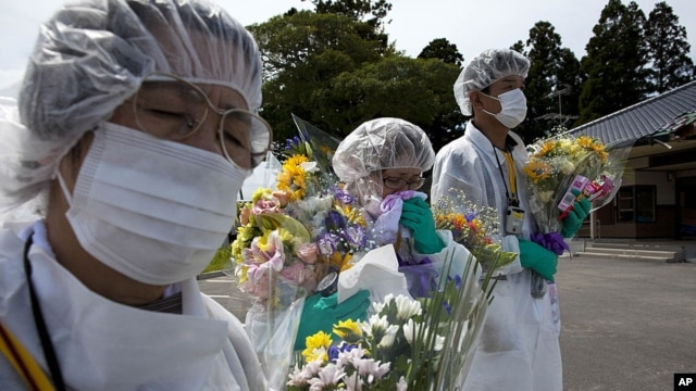 Mourners in protective suits hold flowers at memorial for residents of Okuma, a small town near Fukushima Dai-Ichi nuclear power plant, Japan, July 2011.