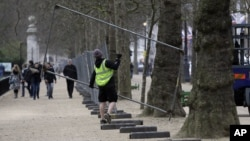 Workers put up fencing in the Mall near Buckingham Palace as preparations begin for the London Marathon, April 18, 2013.