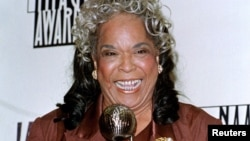 "FILE - Actress Della Reese poses with the Image Award she received as Outstanding Actress in a Drama Television Series for her role in ""Touched by an Angel"" during the National Association for the Advancement of Colored People's 29th annual Image Awards in Pasadena, California, Feb. 14, 1998."