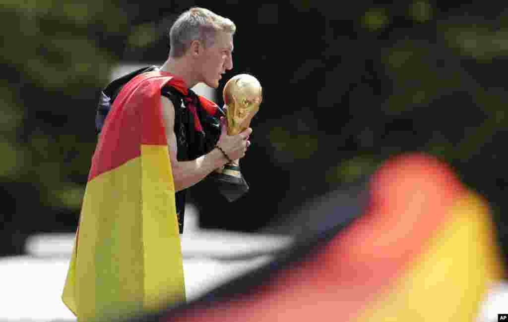 Bastian Schweinsteiger kisses the trophy during theGerman soccer team's World Cup victory celebration, in Berlin, July 15, 2014.