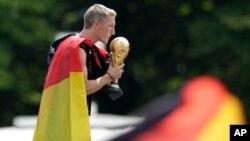 Bastian Schweinsteiger embrasse le trophée de la coupe du monde à l'arrivée de la Mannschaft en Allemagne après le sacre au Brésil, Munich le 15 juillet 2014 (AP Photo/Petr David Josek)