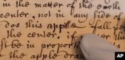 Một trang trong quyển sách tiểu sử Isaac Newton do bạn ông, bác sĩ William Stukeley viết năm 1752, với dòng chữ 'does this apple fall' ('trái táo rơi') miêu tả lúc Newton bắt đầu hiểu định luật vạn vật hấp dẫn (Hình: AP Photo/Lucy Young)