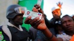 یکی از رای دهندگان هائیتی کارت شناسایی خود را نشان می دهد