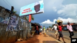 People walk past a campaign poster for incumbent President Ernest Bai Koroma, in Freetown, Sierra Leone, October 19, 2012.