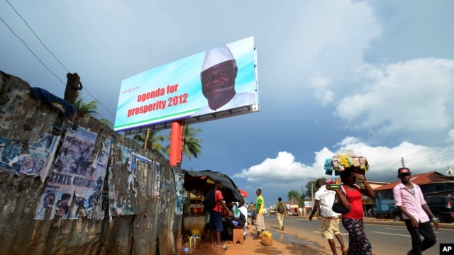 People walk past a campaign poster for incumbent President Ernest Bai Koroma, in Freetown, Sierra Leone, Oct. 19, 2012.