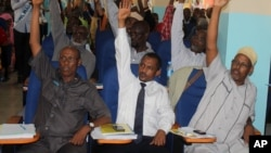 Somali MPs raise their hands during session to impeach Prime Minister Abdi Farah Shirdon, in Mogadishu, Somalia, Dec. 2, 2013.