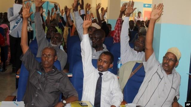 Somali MPs raise their hands during session to impeach Prime Minister Abdi Farah Shirdon, in Mogadishu, Somalia, Dec. 2, 2013.