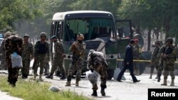 Para petugas memeriksa lokasi serangan bom bunuh diri yang menarget sebuah bus angkatan udara Afghanistan di Kabul (2/7). Delapan perwira dilaporkan tewas dalam insiden tersebut.