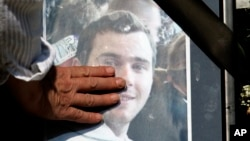 Arhiva - Žena plače i drži fotografiju Brisa Tatona, 28-ogodišnjeg francuskog navijača koji je napadnut i prebijenu Beogradu 1. oktobra 2009, da bi 12 dana kasnije preminuo.