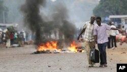 Deux hommes portant une valise, dépassent une barricade de feu à Bujumbura, Burundi, le 30 avril 2015.