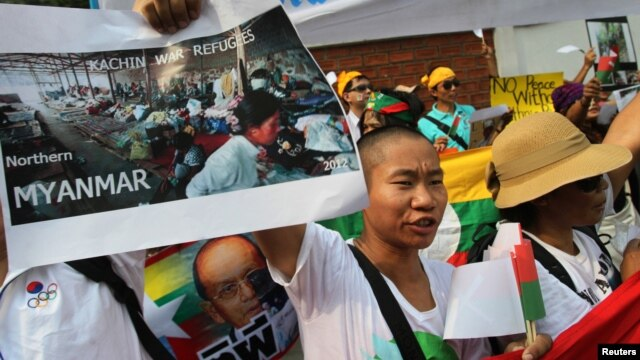 A minority Kachin holds up an image showing Kachin refugees in northern Burma during a protest in front of Burmese Embassy in Bangkok, Thailand, January 11, 2013.