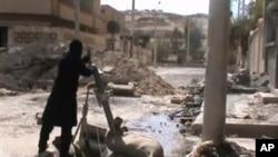 自由叙利亚军战士2013年3月24日在叙利亚大马士革乡间地区将迫击炮弹放在发射管