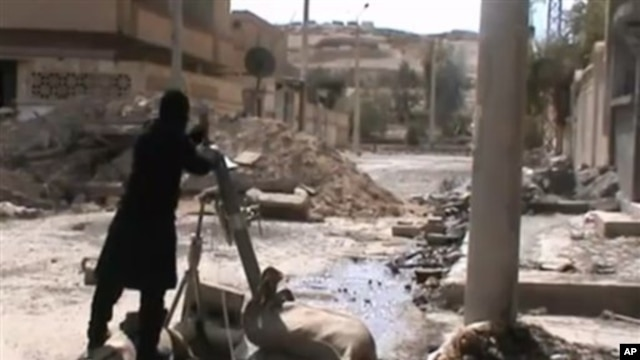 Free Syrian Army fighters drop shell into a firing tube, in Damascus countryside, Syria, Mar 24,2013 (Ugarit News via AP video)