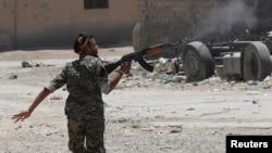 Kurdski borac, pripadnik Jedinica narodne zaštite (YPG) puca iz puške na militante Islamske države dok pretrčava ulicu u Raki, Sirija, 3. juli 2017. (REUTERS/Goran Tomasevic)