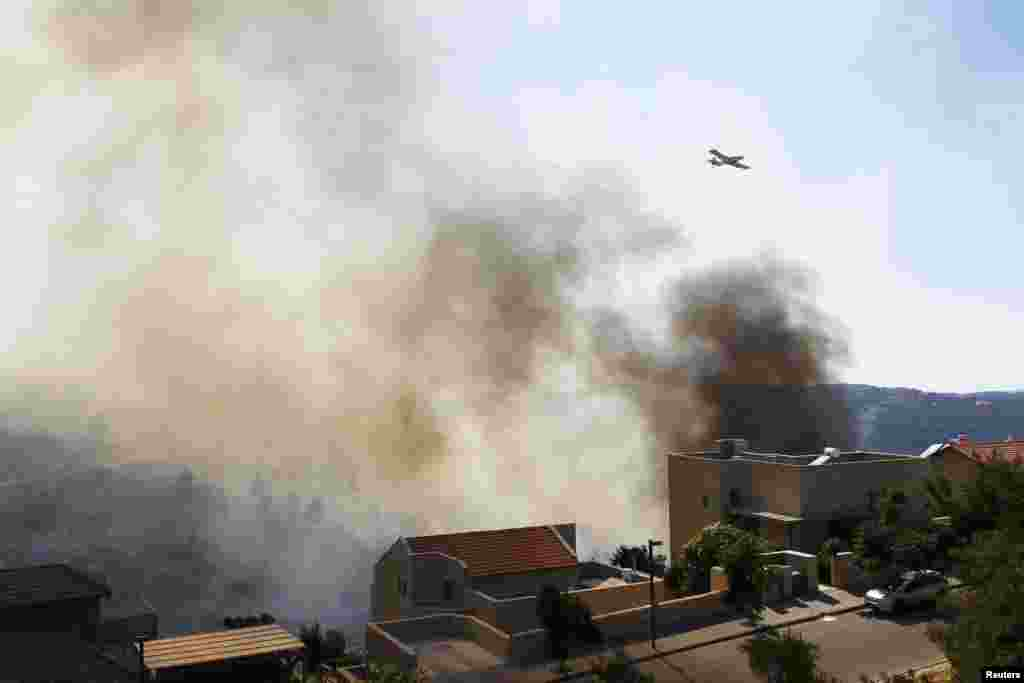 A fire-fighting aircraft works over a forest fire raging near the Israeli village of Aminadav, near Jerusalem, July 2, 2014.