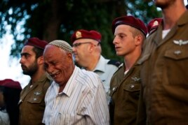 Israeli soldiers and a relative of Israeli soldier Bnaya Rubel mourn during Rubel's funeral in Holon, near Tel Aviv, July 20, 2014.