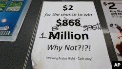 An updated paper sign is displayed the counter of a 7-Eleven store shows that the Mega Millions estimated jackpot has soared to $1 billion Oct. 19, 2018, in Chicago. No one won Friday, and the jackpot is estimated to be $1.6 billion by Tuesday's drawing.