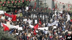 Protesters stand in front of riot police during a demonstration outside the parliamentary building in Tunis November 22, 2011.