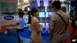 Ảnh minh họa: Nhân viên nói chuyện với khách hàng tại một hội chợ ở Bắc Kinh