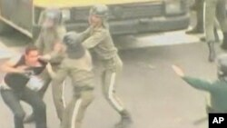 Members of Iran's Revolutionary Guard subdue a protester