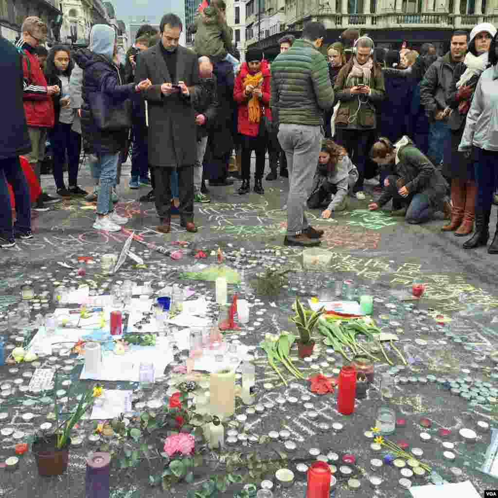 Hundreds of words, drawings, plants and candles now cover the the plaza outside the Bourse – the Belgian stock exchange - following Tuesday 's attacks at Brussels airport and Metro station. (Heather Murdock/VOA)