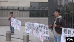 馬永田和她的兒子現身中國駐美國大使館門外拉橫幅抗議。(視頻截圖)