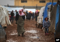 FILE - Syrian walk at a camp near the Bab al-Salam border crossing with Turkey, in Syria, Feb. 6, 2016. Thousands of Syrians have rushed toward the Turkish border, fleeing fierce Syrian government offensives and intense Russian airstrikes.