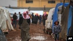 Seorang warga Suriah berjalan di sebuah kamp pengungsi dekat perbatasan Bab al-Salam, Suriah-Turki, di Suriah, 6 Februari 2016. Ribuan warga Suriah mendekati perbatasan Turki, menghindari serangan udara pasukan pro-pemerintah Suriah yang dibantu oleh Rusia.