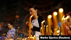 Seorang perempuan menyalakan lilin selama kebaktian Paskah Ortodoks di Biara St. Sava di Beograd 5 Mei 2013. (Foto: REUTERS/Marko Djurica)
