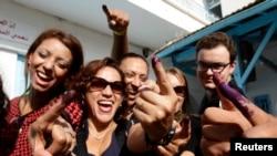 Des Tunisiens montrent leurs doigts colorés après avoir exprimé leur voix, à Tunis le 26 octobre 2014.